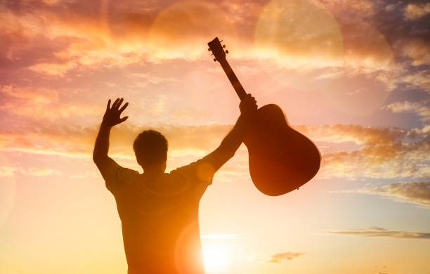 Silhouette of guitarist musician holding guitar against sunset stock photo