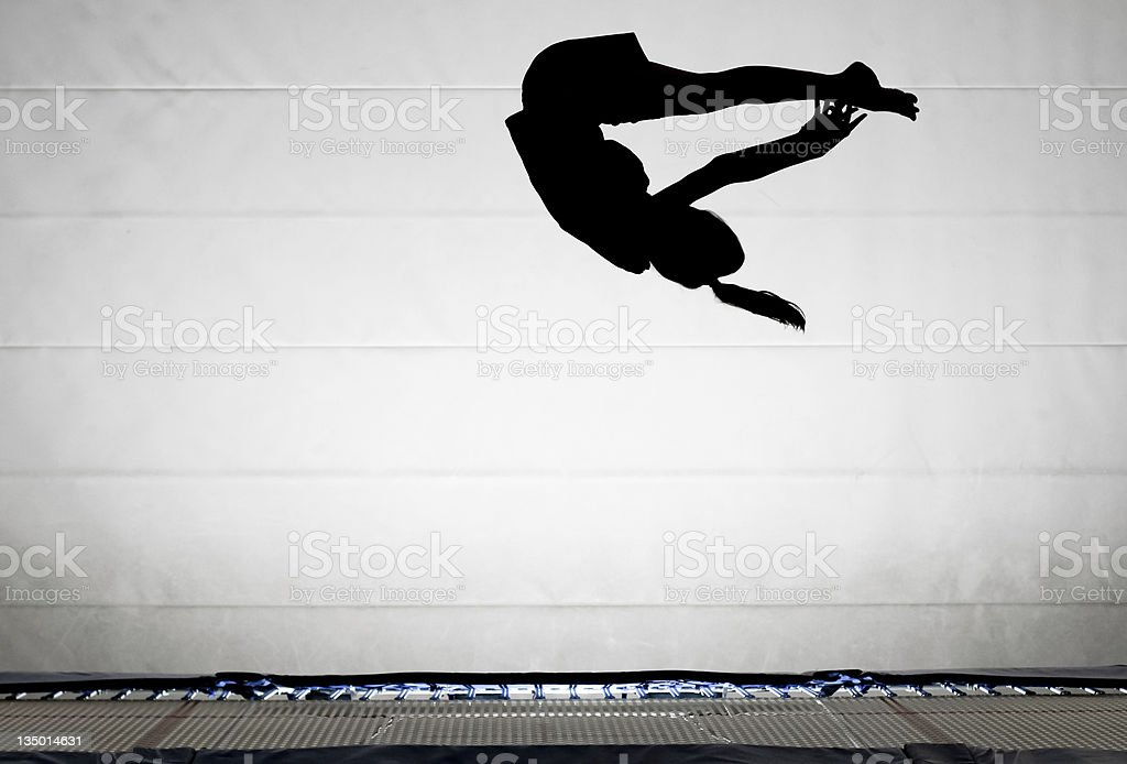 Silhouette of gymnast performing pike somersault stock photo