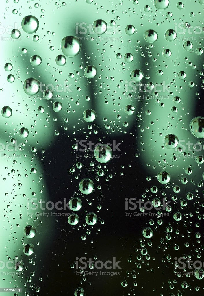 Silhouette of hand behind wet window royalty-free stock photo