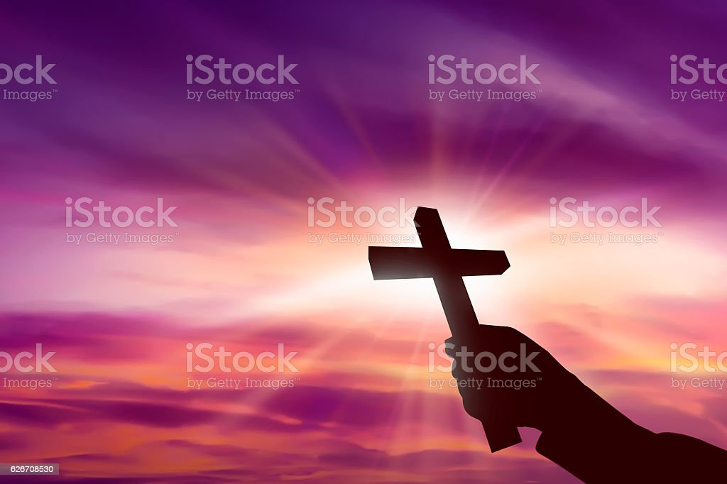 Silhouette of hand holding christian cross stock photo