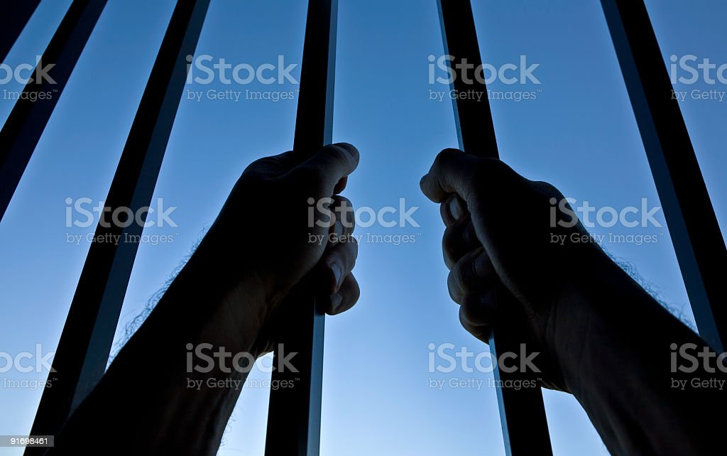 Silhouette of Hands Behind Jail Bars Against Clear Blue Sky royalty-free stock photo