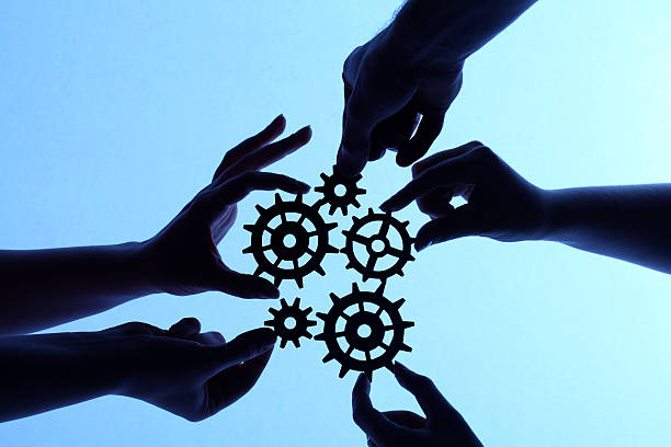 silhouette of hands holding cogs and gears - cog stock photos and pictures