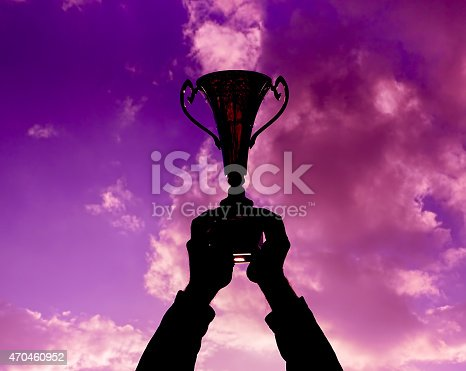 544347868 istock photo Silhouette of hands holding up a trophy against sky 470460952