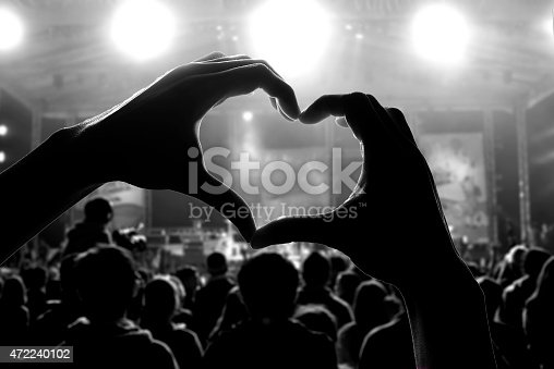 istock Silhouette of hands making a heart at a concert 472240102