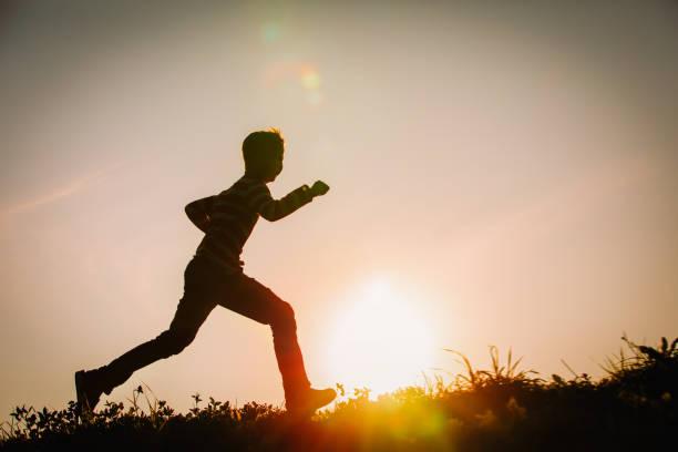 Silhouette des glücklichen Jungen läuft bei Sonnenuntergang Natur – Foto