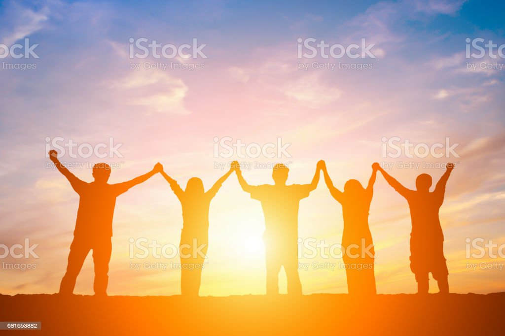 Silhouette of happy business team making high hands in sunset sky background for business teamwork concept. stock photo