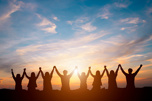 istock Silhouette of happy business team making high hands in sunset sky background for business teamwork concept 696209402