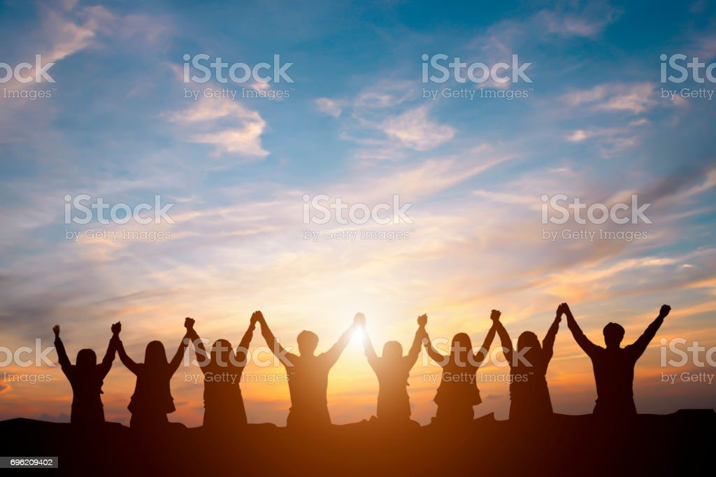Silhouette of happy business team making high hands in sunset sky background for business teamwork concept - foto stock