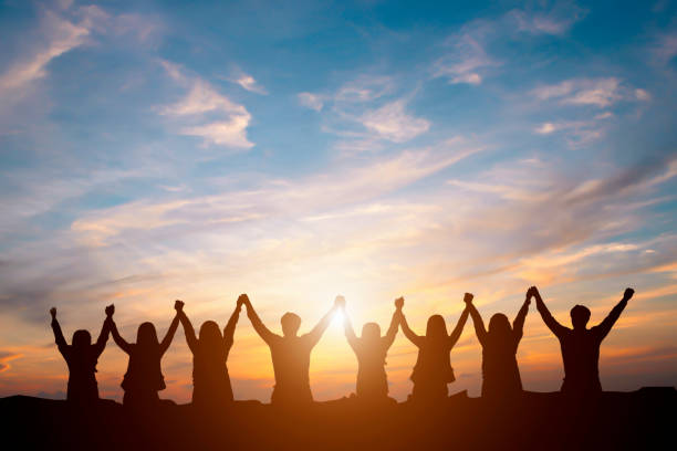 silhouette of happy business team making high hands in sunset sky background for business teamwork concept - teamwork stock photos and pictures