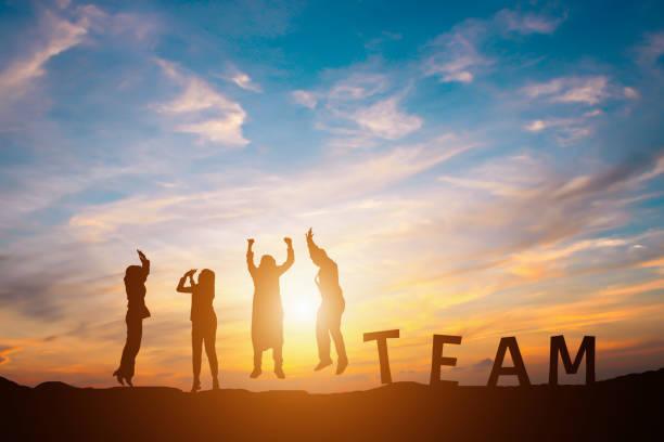 Silhouette der glücklich Business Team macht hohe Hände im Sonnenuntergang Himmel – Foto