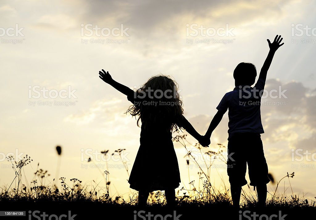 Silhouette of happy children playing in the meadow at sunset stock photo
