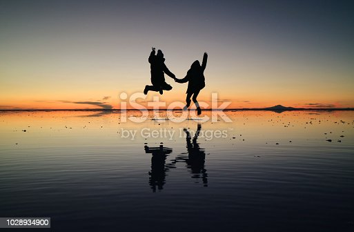 istock Silhouette of happy couple jumping on the amazing mirror effect of Uyuni Salt Flats against sunset sky, Bolivia, South America 1028934900