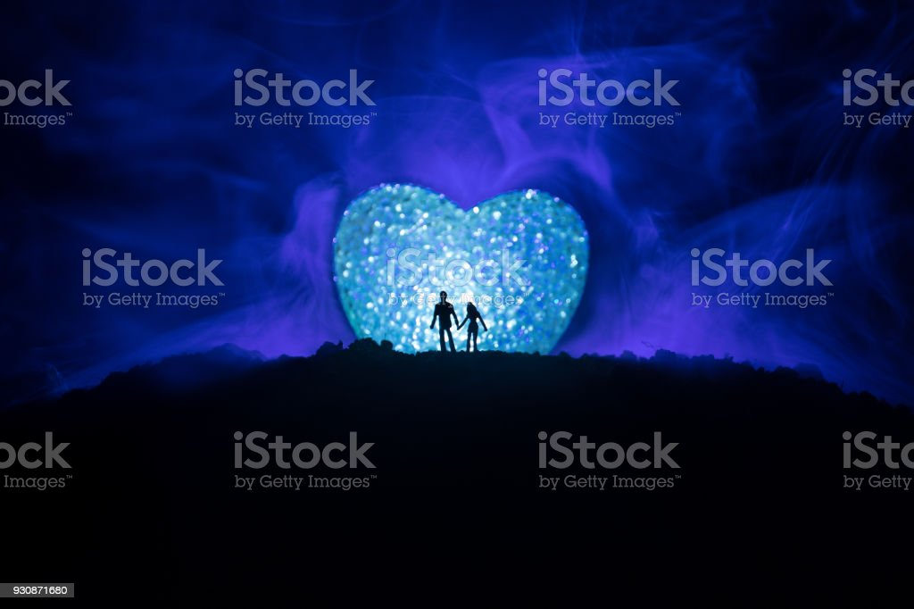 Silhouette Of Happy Couple Standing Behind Big Shaped Heart Symbol