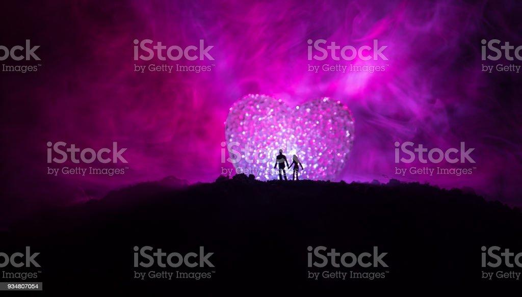 밤에 산에 큰 모양의 심장 기호 뒤에 서 있는 행복 한 커플의 실루엣. 안개가 하늘에 빛나는 달 처럼 큰 심장입니다. 발렌타인의 날 장식 사진 - 로열티 프리 2명 스톡 사진