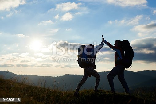 Silhouette of happy couple with backpacks on top of the mountain give each other a high five against the background of the mountains and the cloudy sky with a bright sun at sunset. Bottom view