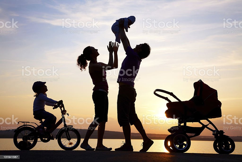 Silhouette of happy family playing at sea coast royalty-free stock photo