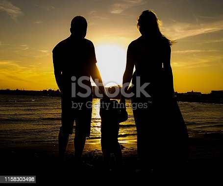 Silhouette of happy family  standing on beach against sky during sunset. Father, mother and daughter who are holding their hands