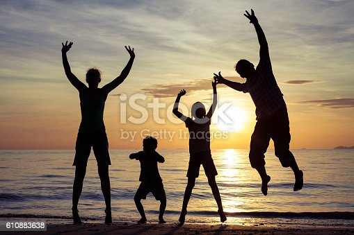 586180632istockphoto Silhouette of happy family who playing on the beach. 610883638