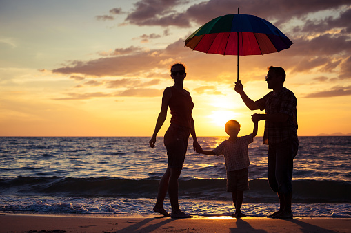Silhouette of happy family who playing on the beach