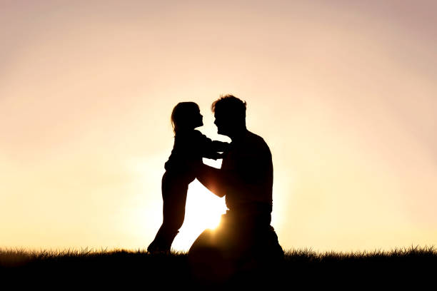Silhouette of Happy Father and his Little Child Smiling and Playing at Sunset stock photo