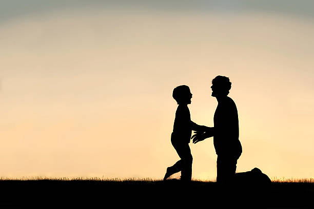 Silhouette of Happy Father and Son at Sunset stock photo
