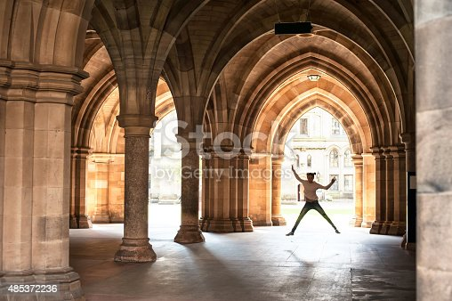 istock Silhouette of happy girl jumping in cloisters of Glasgow University. 485372236