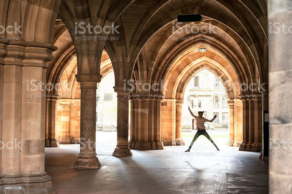 Silhouette of happy girl jumping in cloisters of Glasgow University. stock photo