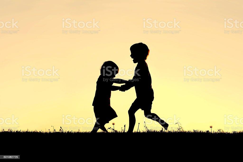 Silhouette de heureux petits enfants dansant au coucher du soleil - Photo