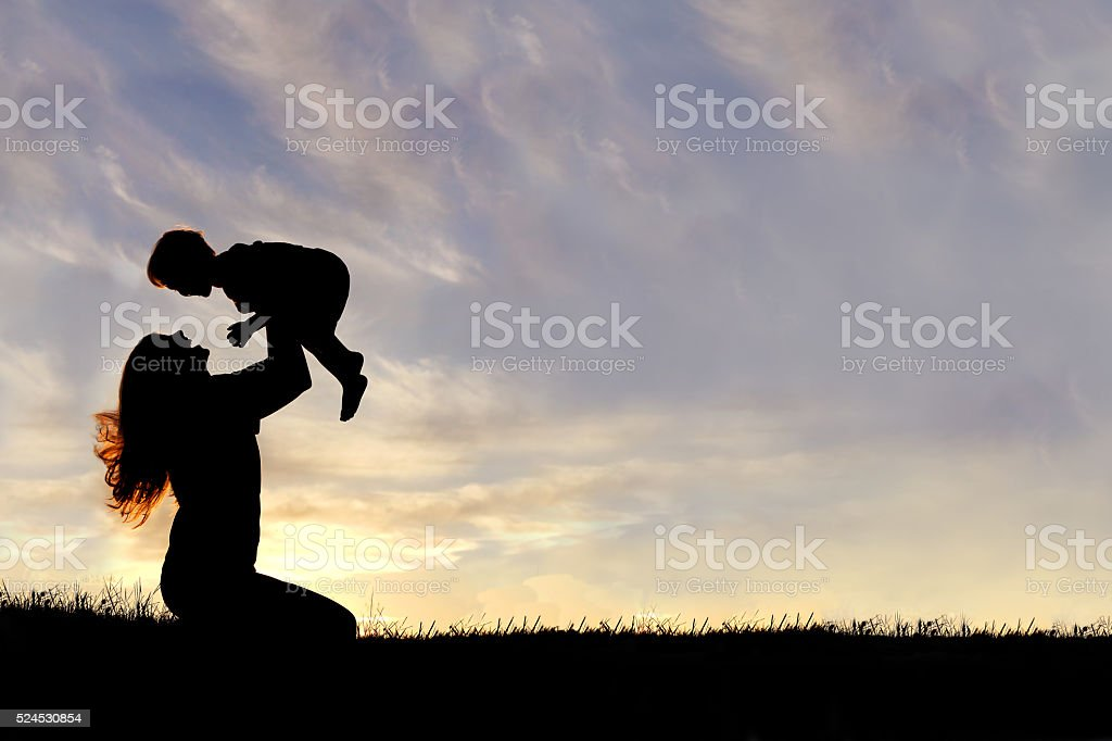 Silhouette of Happy Mother Playing Outside with Baby stock photo