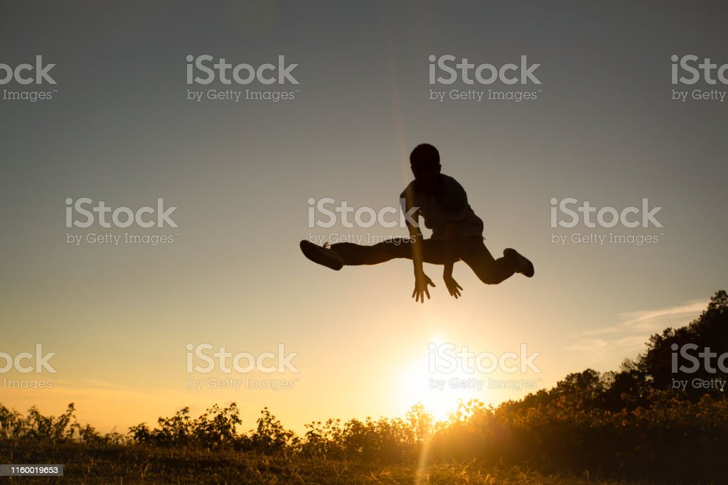 Silhouette of happy people jumping in sunset on the Moutain.