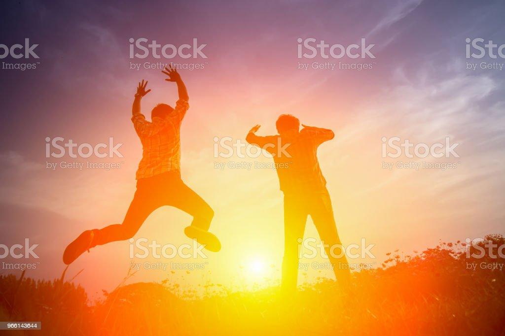 Siluett av glada människor hoppa i solnedgången. - Royaltyfri Aktiv livsstil Bildbanksbilder