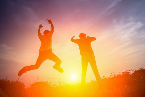 Silhouette Of Happy People Jumping In Sunset Stock Photo - Download Image Now