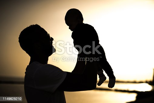 Silhouette of happy that holding his baby boy in the air.