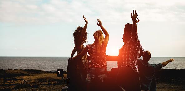 Silueta De Amigos Turistas Felices Haciendo Excursión Siguiente La Playa Convertible 4 X 4 Coche Jóvenes Que Se Divierten Viajando Juntos Amistad Y Vacaciones Concepto Foco En Los Chicos Del Centro Foto de stock y más banco de imágenes de A la moda