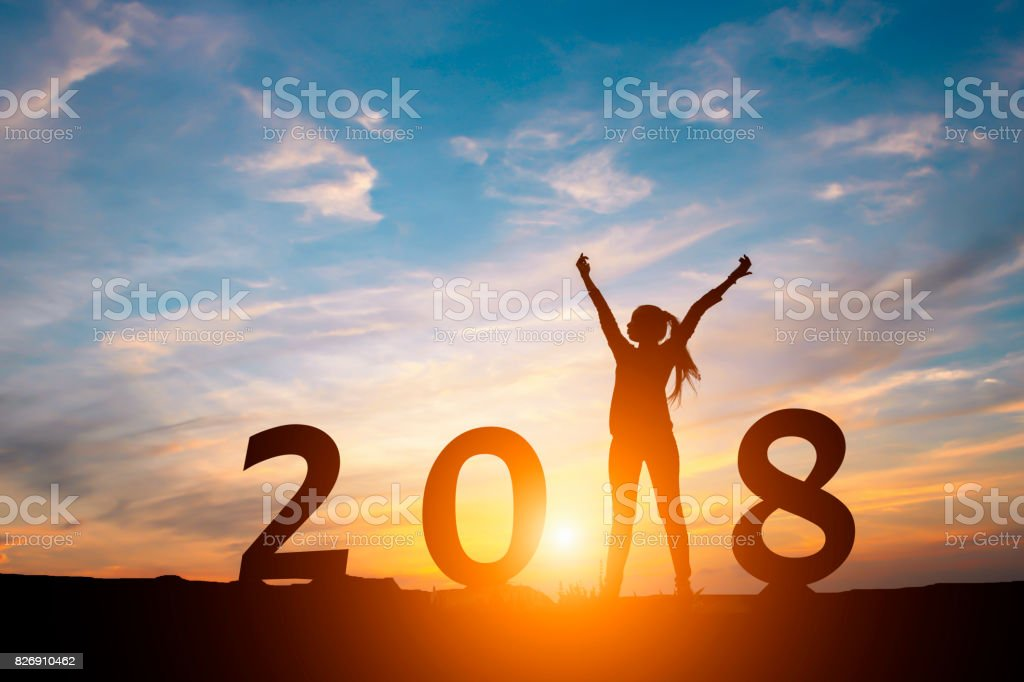 Silhouette of happy woman with New yeay 2018 concept in sunset background. stock photo