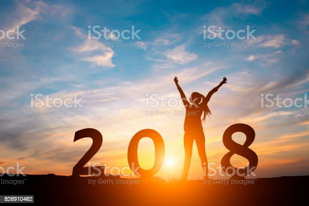 Silhouette of happy woman with New yeay 2018 concept in sunset background.