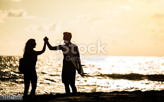 Silhouette of happy young couple going surfing and holding hands.