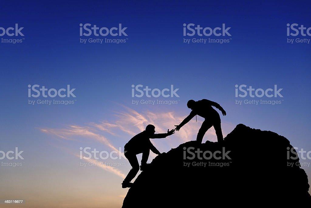 Silueta de ayudar a mano entre dos escalador - foto de stock