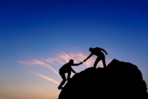 silhouette of helping hand between two climber - help single word stock photos and pictures