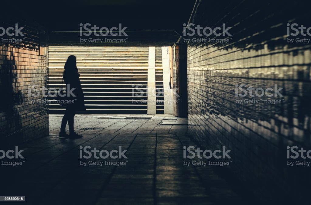 Silhouette of hipster woman in tunnel stock photo