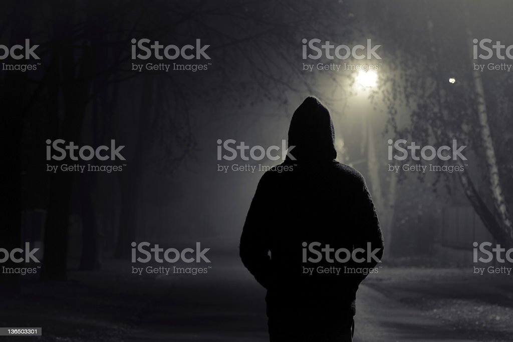 Silhouette of hooded person with spooky dark background Stranger walking the streets on a cold foggy night Burglar Stock Photo
