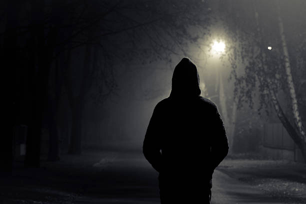 Silhouette of hooded person with spooky dark background Stranger walking the streets on a cold foggy night stranger stock pictures, royalty-free photos & images