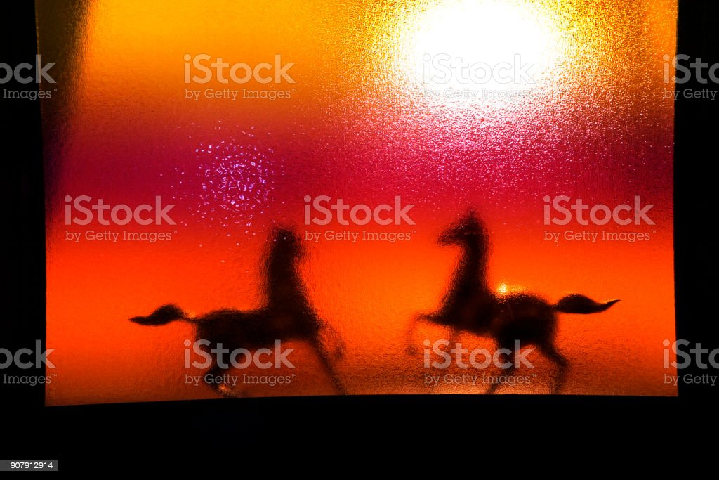silhouette of horses behind the mirror stock photo