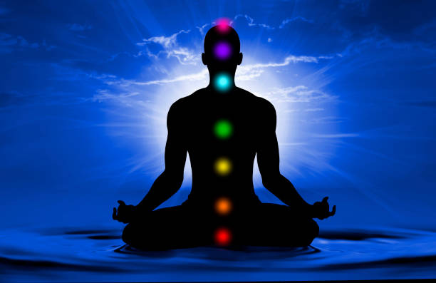 silhouette of human doing yoga and where has scored seven chakra points - aura stock photos and pictures