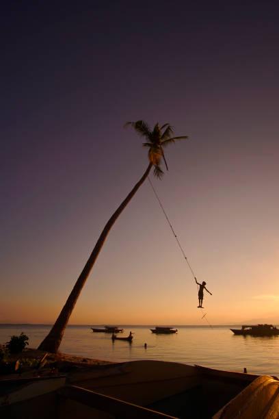 Silhouette von Indentify Bajau Kids spielen eine Schaukel unter Kokosnussbaum bei Sonnenuntergang auf Maiga Island, Sempoerna – Foto