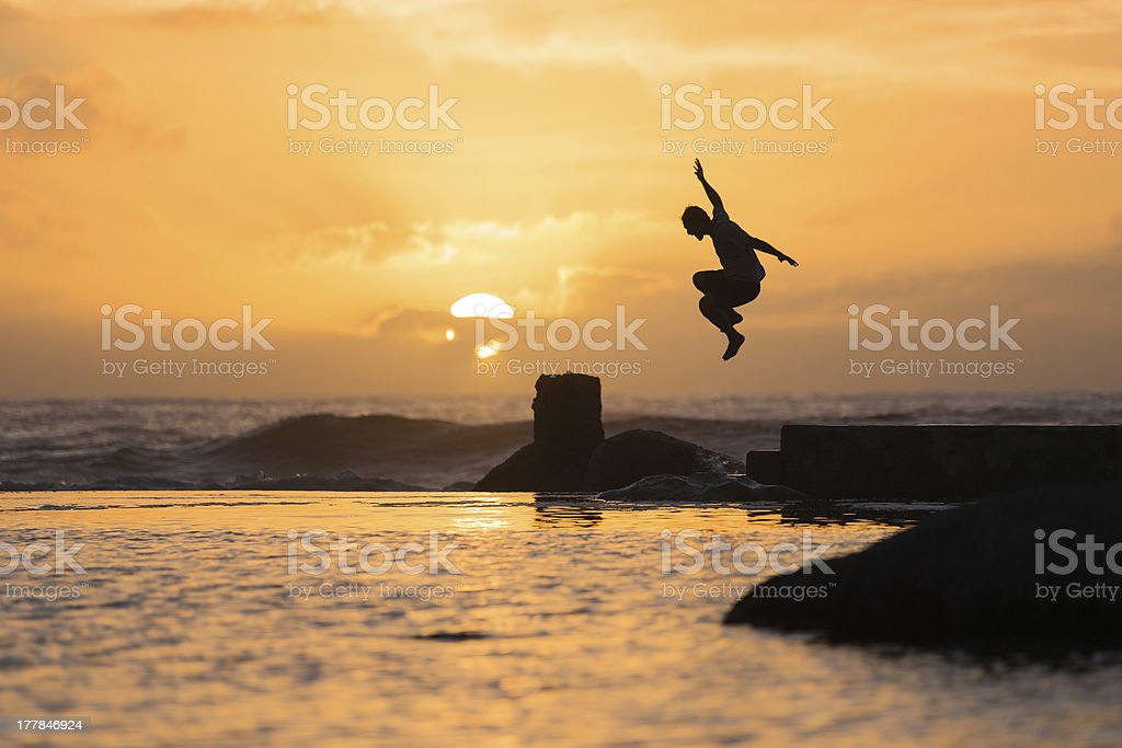 Silhouette of Jumping Man at Sunset stock photo