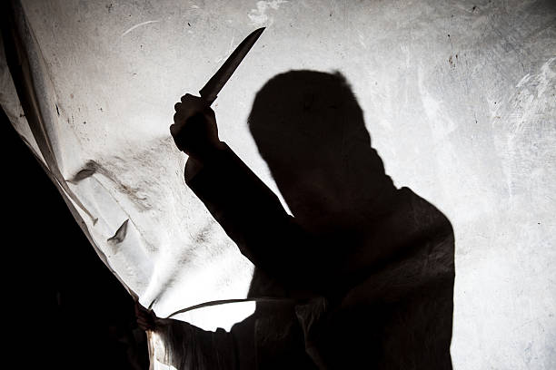 Silhouette of killer with knife in action stock photo