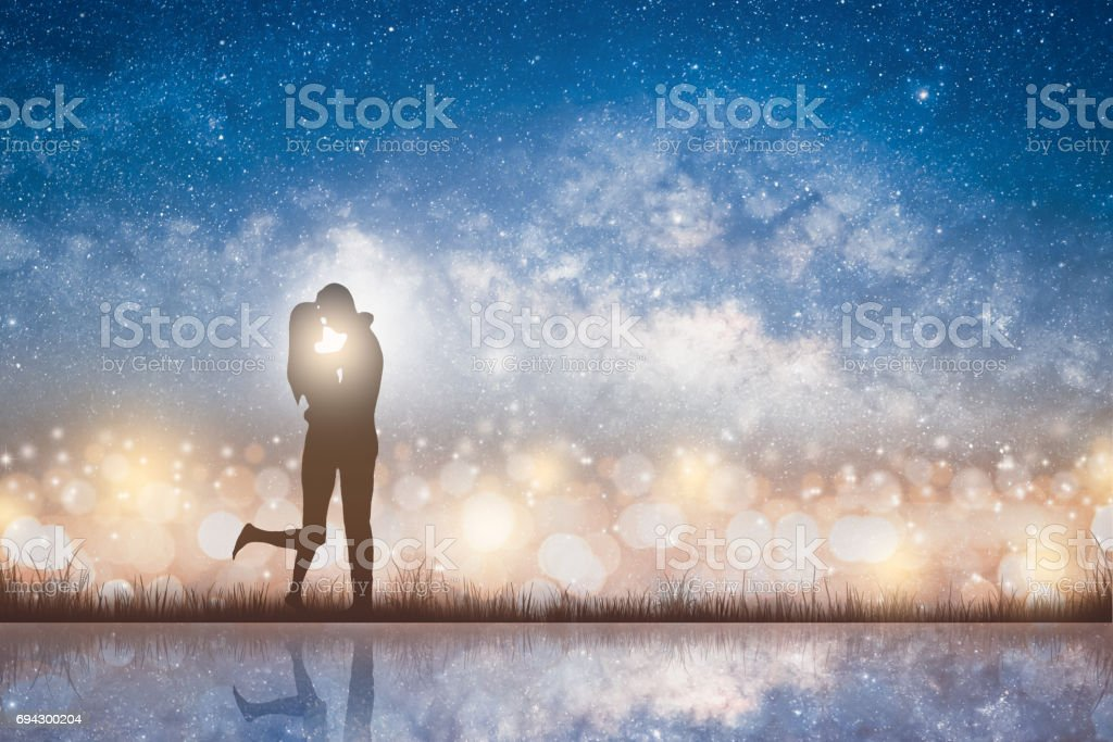 Silhouette of kissing couple love on the starry night sky stock photo