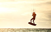 Silhouette of mid adult kiteboard surfer flying in the air.