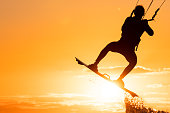 Silhouette of kitesurfer jumping in beautiful yellow sunset conditions with the sun right below his board